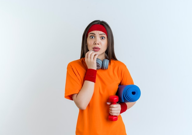 Impressed young sporty woman wearing headband and wristbands and headphones on neck holding dumbbell with yoga mat touching chin looking isolated