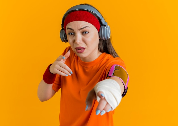 Impressed young sporty woman wearing headband and wristbands and headphones