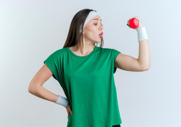 Impressionato giovane donna sportiva che indossa la fascia e braccialetti che tengono il manubrio tenendo la mano sulla vita guardando i suoi muscoli