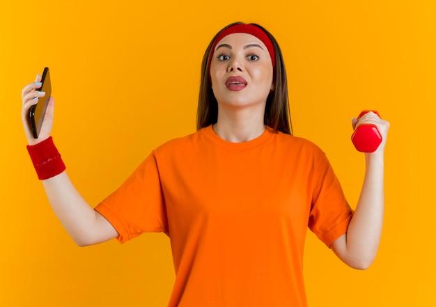 Impressionato giovane donna sportiva che indossa fascia e braccialetti in possesso di manubri e telefono cellulare alla ricerca