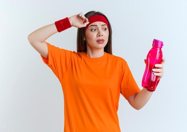Impressionato giovane donna sportiva che indossa fascia e braccialetti che tengono e guardando la bottiglia d'acqua toccando la testa