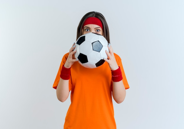 Impressed young sporty woman wearing headband and wristbands holding soccer ball looking from behind it isolated