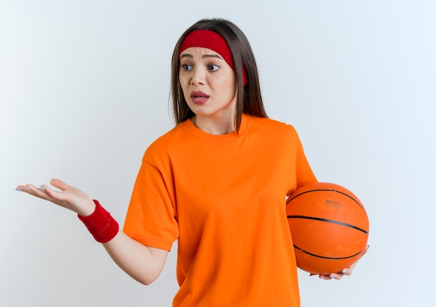 Impressed young sporty woman wearing headband and wristbands showing empty hand looking at side holding basketball ball