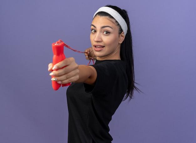 Impressionato giovane donna sportiva che indossa fascia e braccialetti in piedi in vista di profilo tirando la corda per saltare allungandola verso la parte anteriore guardando la parte anteriore isolata sul muro viola