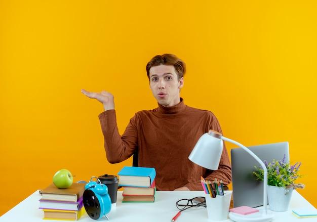 学校の道具を持って机に座っている感動した若い学生の男の子は、手を左右に向けます