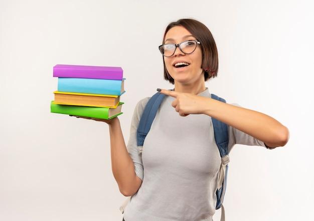 白で隔離された本を保持し、指している眼鏡とバックバッグを身に着けている感動の若い学生の女の子