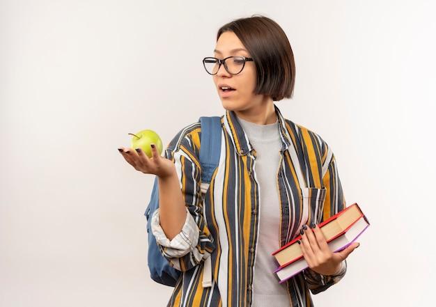 白で隔離されるリンゴを見て本とリンゴを保持している眼鏡とバックバッグを身に着けている感動の若い学生の女の子