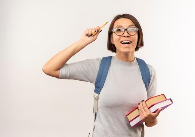 本を保持し、白で隔離のペンを上げる眼鏡とバックバッグを身に着けている感動の若い学生の女の子