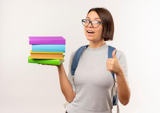白で隔離の親指を示す本を保持している眼鏡とバックバッグを身に着けている感動の若い学生の女の子