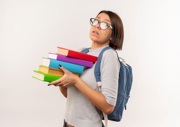 白で隔離の本を保持している縦断ビューで立っている眼鏡とバックバッグを身に着けている感動の若い学生の女の子