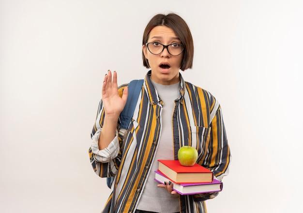 Impressionato giovane studente ragazza con gli occhiali e borsa posteriore in possesso di libri e mela su di loro alzando la mano isolata su bianco