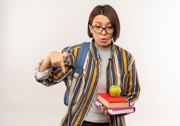 Impressionato giovane studente ragazza con gli occhiali e borsa posteriore in possesso di libri con la mela su di esso che punta e guarda verso il basso isolato su bianco