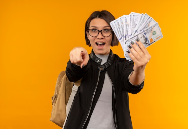 Ragazza giovane studentessa impressionata con gli occhiali e borsa posteriore che tiene i soldi e che indica nella parte anteriore isolata sull'arancio