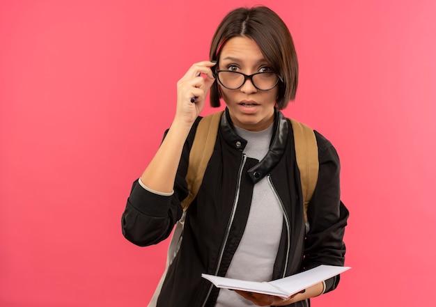 Impressionato giovane studente ragazza con gli occhiali e borsa posteriore tenendo il blocco note e mettendo la mano sui vetri isolati sul colore rosa