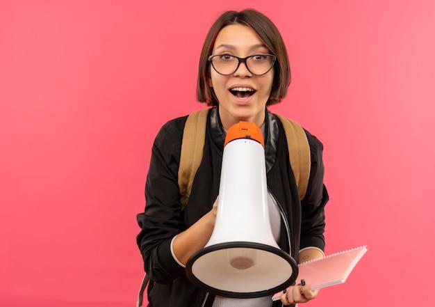 Impressionato giovane studente ragazza con gli occhiali e borsa posteriore tenendo appunti e altoparlante isolato sul rosa