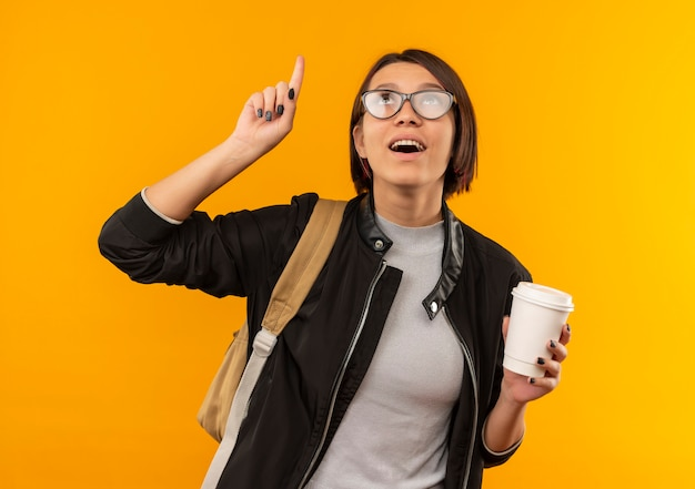 Impressed young student girl wearing glasses and back bag holding plastic coffee cup pointing and looking up isolated on orange