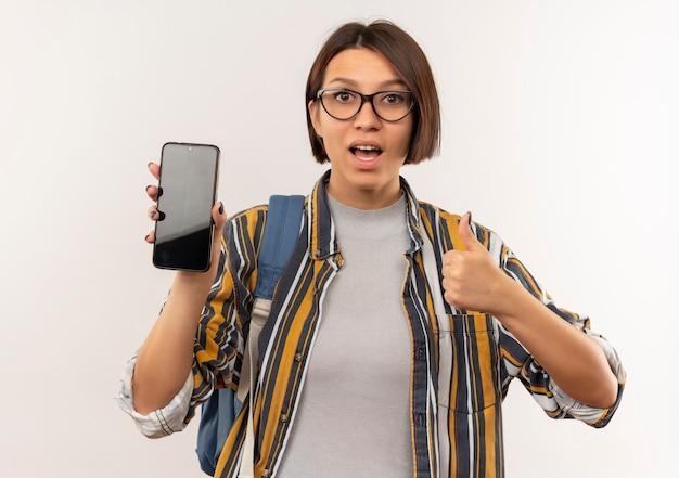 Impressionato giovane studente ragazza con gli occhiali e borsa posteriore che mostra il telefono cellulare e il pollice in alto isolato su bianco
