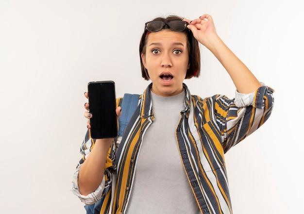 Impressionato giovane studente ragazza con gli occhiali sulla testa e borsa posteriore che mostra i vetri della tenuta del telefono cellulare isolati su bianco