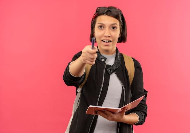 ピンクで隔離のペンで正面を指しているメモ帳を保持している頭とバックバッグに眼鏡をかけている感動の若い学生の女の子