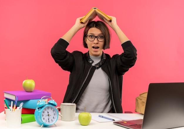 ピンクで隔離された頭の上の本を維持する宿題をしている机に座って眼鏡をかけている感銘を受けた若い学生の女の子