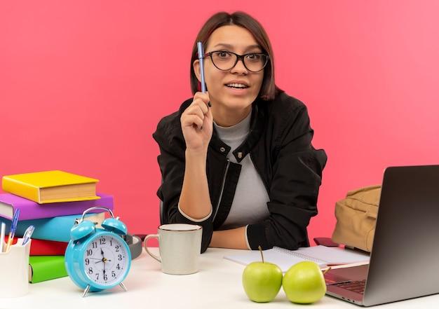 Впечатленная молодая студентка в очках сидит за столом, держа ручку и делает домашнее задание, изолированное на розовом