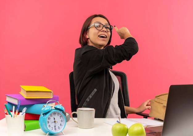 Impressionato giovane studente ragazza con gli occhiali seduto alla scrivania a fare i compiti che punta dietro isolato sul rosa