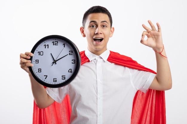 Впечатлен молодой мальчик-супергерой в красном плаще, держащий часы, смотрящий в камеру, делает знак ок, изолированные на белом фоне