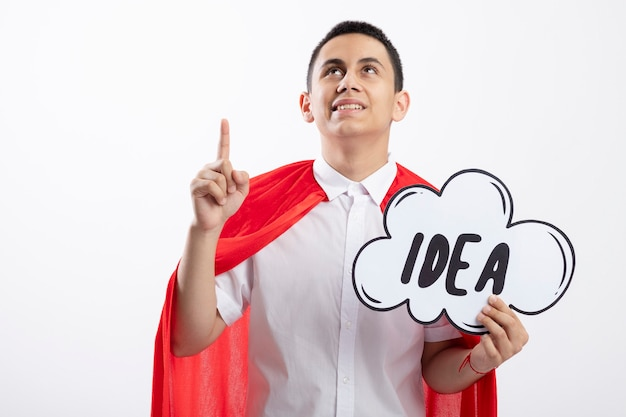 Impressed young superhero boy in red cape holding idea bubble looking and pointing up isolated on white background with copy space