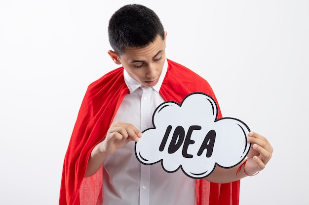 Impressed young superhero boy in red cape holding and looking at idea bubble isolated on white background