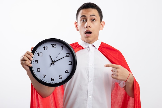 Impressed young superhero boy in red cape looking at camera holding and pointing at clock isolated on white background