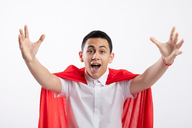 Impressed young superhero boy in red cape looking at camera stretching out hands towards camera isolated on white background