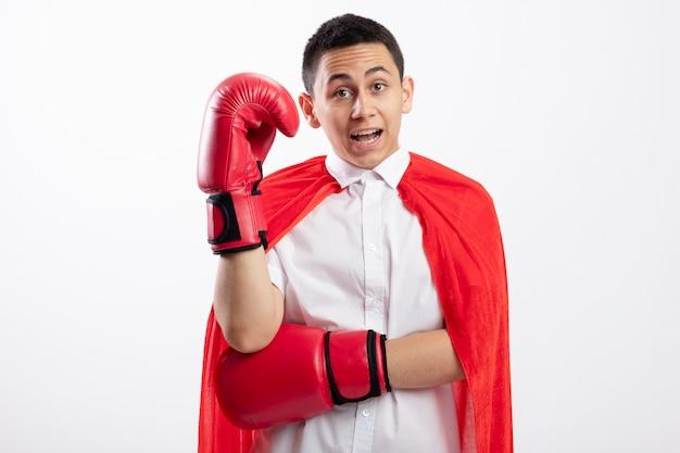 Colpito il giovane ragazzo del supereroe in mantello rosso che indossa i guanti di scatola che guarda l'obbiettivo tenendo la mano in aria isolata su fondo bianco con lo spazio della copia