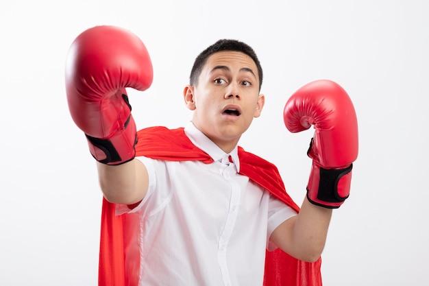 Impressionato giovane supereroe ragazzo in mantello rosso che indossa i guanti di scatola guardando il lato tenendo la mano in aria allungando un'altra mano verso la telecamera isolata su sfondo bianco