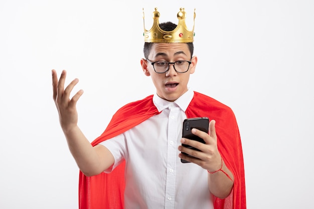 Impressed young superhero boy in red cape wearing glasses and crown holding and looking at mobile phone keeping hand in air isolated on white background