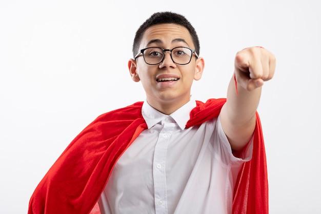 Impressionato giovane supereroe ragazzo in mantello rosso con gli occhiali guardando e indicando la fotocamera isolata su sfondo bianco