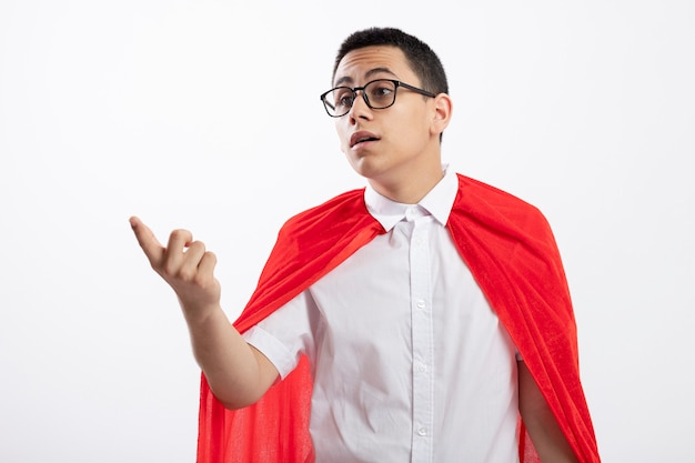 Impressed young superhero boy in red cape wearing glasses looking and pointing at side isolated on white background