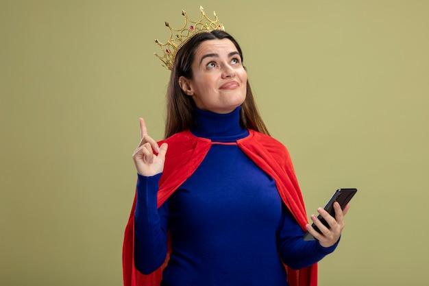 Impressionato giovane ragazza del supereroe alzando lo sguardo indossando corona tenendo il telefono e indica in alto isolato su sfondo verde oliva
