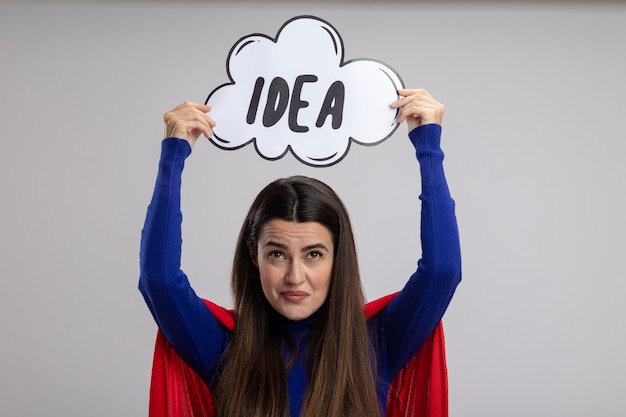 흰색 배경에 고립 된 아이디어 거품을 올리는 감동 된 젊은 슈퍼 히어로 소녀