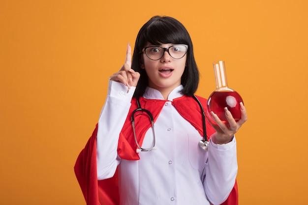 Stetoscopio da portare della giovane ragazza del supereroe impressionato con la veste medica e il mantello con gli occhiali che tengono la bottiglia di vetro di chimica riempita di liquido rosso