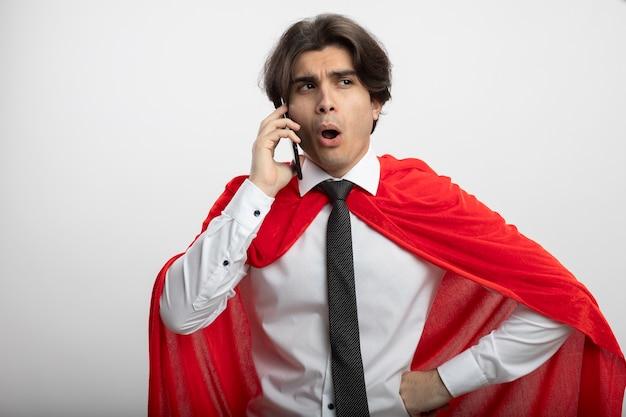 ネクタイを身に着けている側を見て感動した若いスーパーヒーローの男は電話で話し、白で隔離された腰に手を置く