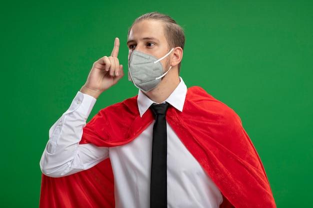 의료 마스크와 넥타이를 착용하고 녹색에 고립 된 최대 포인트에 감동 젊은 슈퍼 히어로 남자
