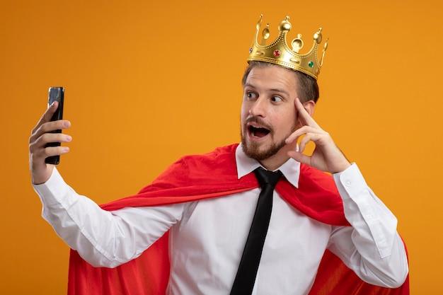 ネクタイと王冠を身に着けている感銘を受けた若いスーパーヒーローの男は、オレンジ色に分離された自撮り写真を撮ります