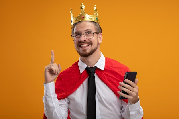 ネクタイと王冠を身に着けている印象的な若いスーパーヒーローの男は、オレンジ色の背景に分離された電話とポイントを保持している眼鏡で