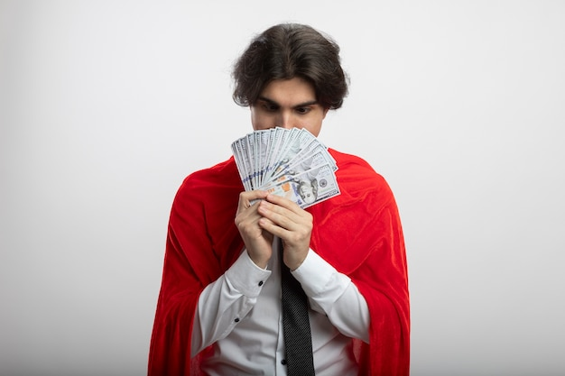 Impressed young superhero guy wearing tie covered face with money isolated on white
