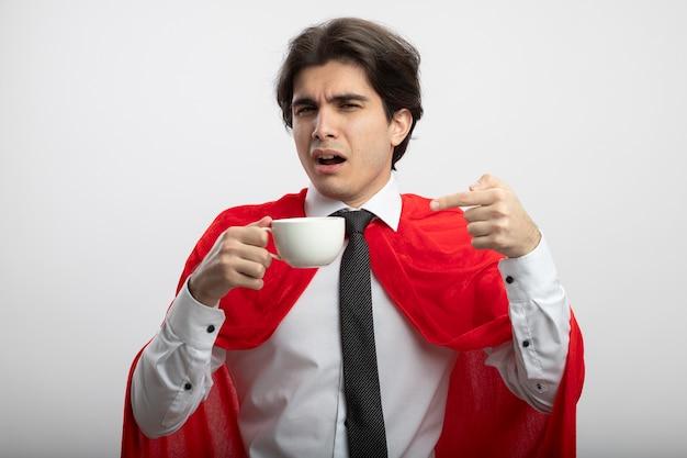 白い背景で隔離のコーヒーのカップを保持し、ポイントを保持しているネクタイを身に着けている印象的な若いスーパーヒーローの男