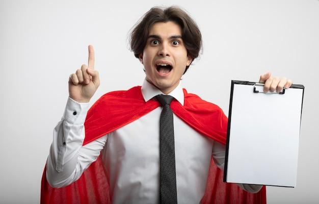 Ragazzo giovane supereroe impressionato che indossa la cravatta che tiene appunti e indica in alto isolato su sfondo bianco