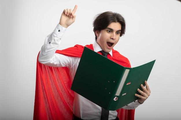 Ragazzo giovane supereroe impressionato che indossa la cravatta che tiene e guardando i punti della cartella in alto isolato su priorità bassa bianca