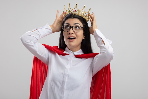 眼鏡をかけ、白い壁に孤立して見上げる王冠に触れる王冠を身に着けている感動の若いスーパーウーマン