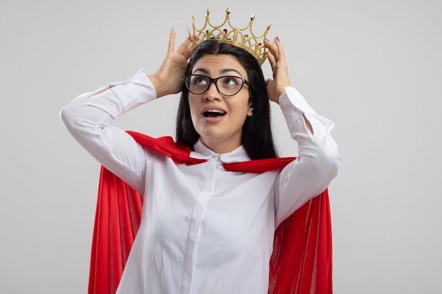 Impressionato giovane superdonna con gli occhiali e corona toccando la corona alzando lo sguardo isolato sul muro bianco