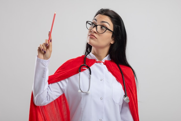 Impressed young superwoman wearing glasses and stethoscope holding and looking at red pencil isolated on white wall